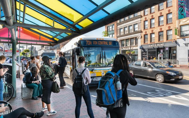 Riders wait on Massachusetts Ave in Central Square, Cambridge, while a 70A bus pulls up to the stop.