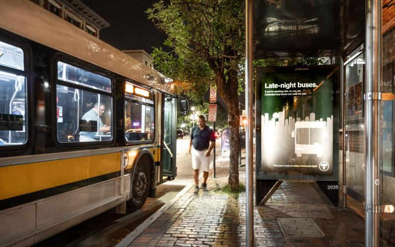 "A bus pulled up to a bus shelter late at night, with a rider walking away, and an ad for late night bus service on the shelter wall, which reads, ""Late-night buses. If you're working late, so are we. Extended bus hours are here for you.""."