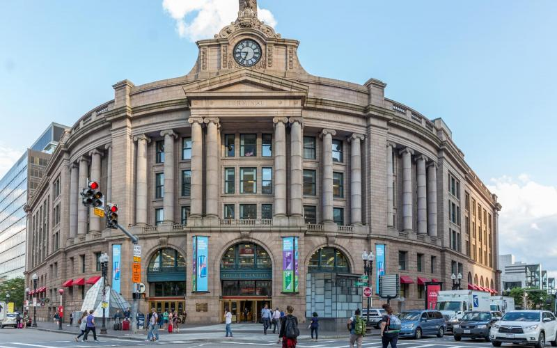 The facade of South Station, with pedestrians and traffic also pictured.