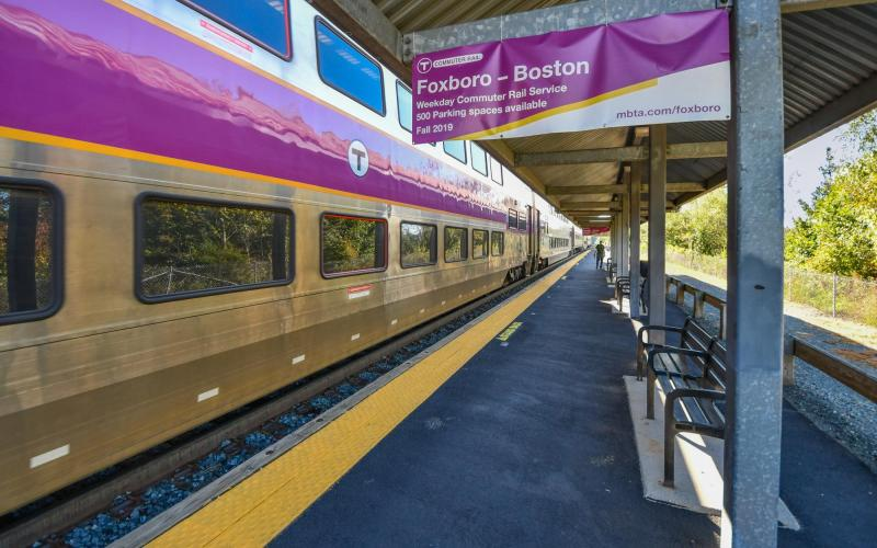 A Commuter Rail train at Foxboro Station's platform, with an advertisting sign for the Foxboro - Boston weekday pilot in the foreground.