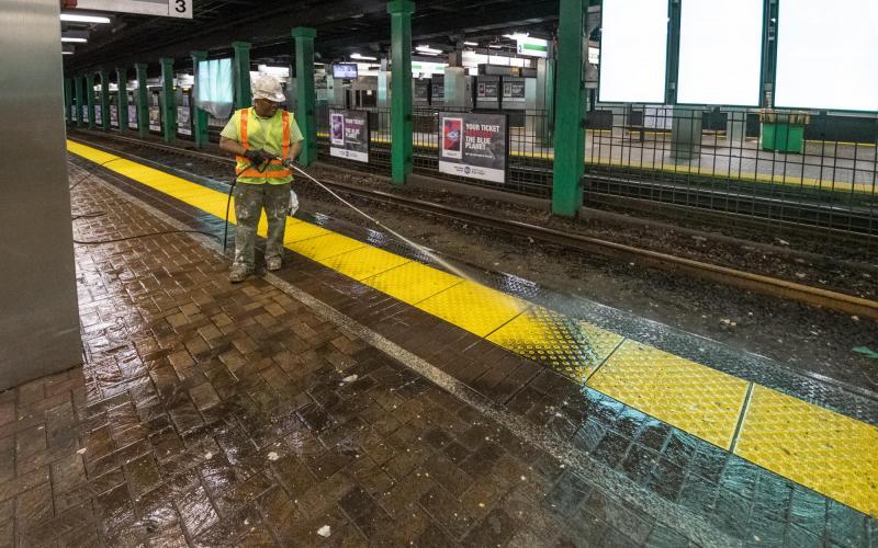 An MBTA worker cleans the Green Line platform at Park Street.