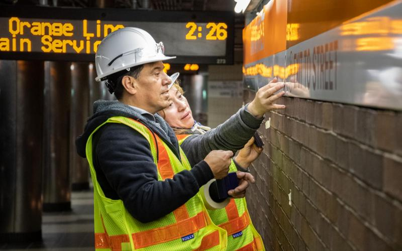 Crew members install new wayfinding signs on the Haymarket platform during the November 1 – 3, 2019 weekend shutdown