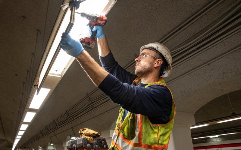 A crew member replaces a light fixture at Downtown Crossing as part of the Red Line beautifucation and track work during the November 15 – 17 weekend shutdown