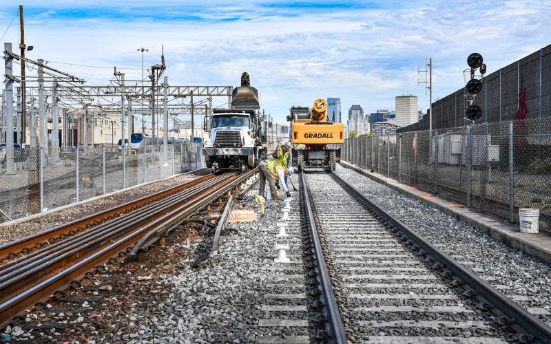 Crew members prepare to install third rail alongside the new Red Line track at Cabot Yard