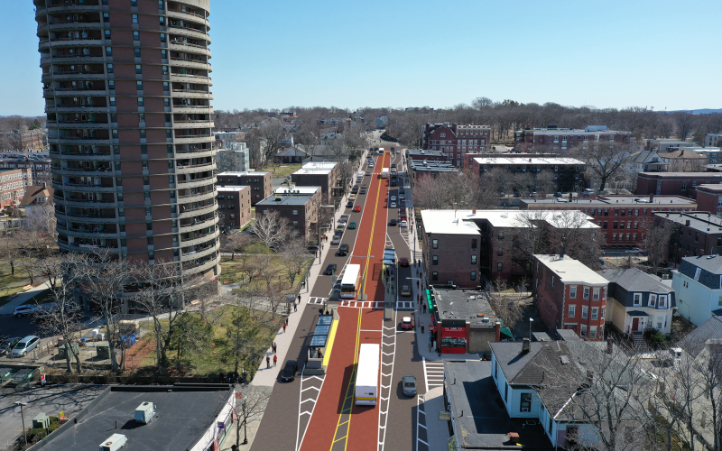 Aerial view of red bus lanes running down the center of Columbus Avenue in Boston. Clear sky and normal traffic conditions.