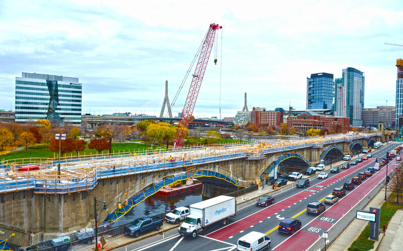 Crews working on the Lechmere Viaduct Rehabilitation with the city and fall foliage in the background