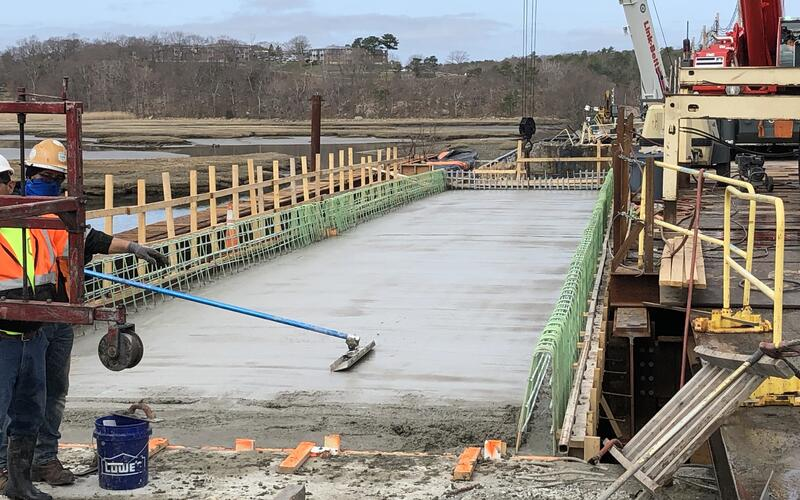 A construction worker is smoothing out a large area of wet concrete