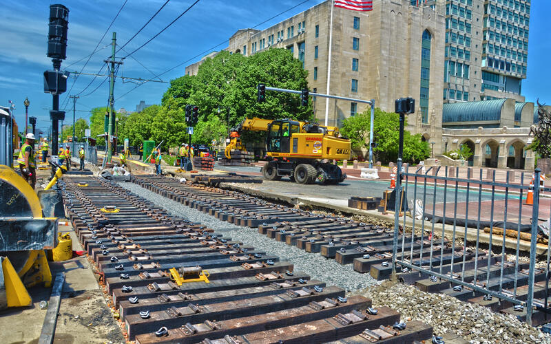 Two long rows of wooden rail ties laid out with constructions workers standing by ready to install them