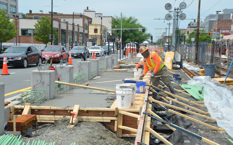 A photo of construction workers smoothing cement in a wooden framework. This will be a platform for a new Green Line B branch station