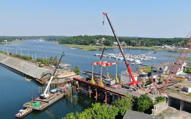 Wide view of the Annisquam River looking upriver showing the cranes supporting the span placement.