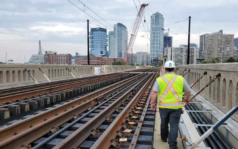 A construction worker standing on the Lechmere Viaduct bridge with his back facing the camera. The bridge is under construction