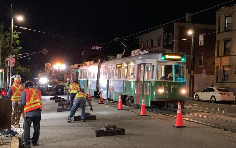 Construction workers in high vis next to a Green Line train at night