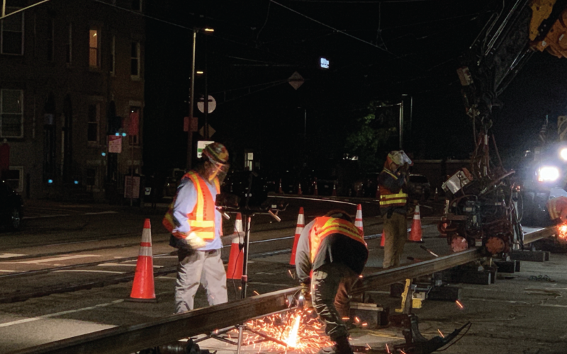 Crews continue welded rail fabrication on the E Branch at night under floodlights