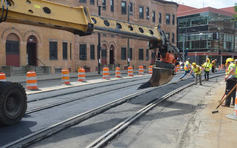 Crews laying down pavement between new tracks on Huntington Ave