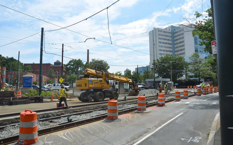 A photo of track work on South Huntington Ave. Construction workers in high vis vests and hard hats are working near a pile of gravel next to the tracks