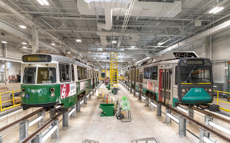 A photo of green line trolley cars at a GLX testing facility. The train on the left is new, and the one on the right is old. They are both elevated on rails inside of a brightly lit warehouse