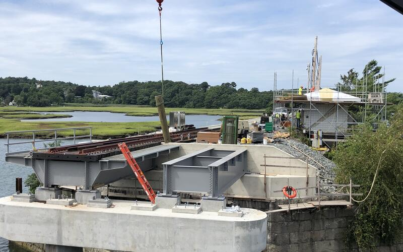 The western approach span leading to the bridge is shown in place. The waterway is at left.