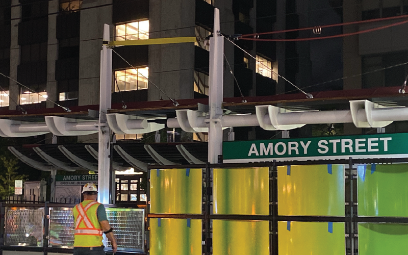 A construction worker in high visibility clothing and a hard hat stands facing the new Amory Street platform at night