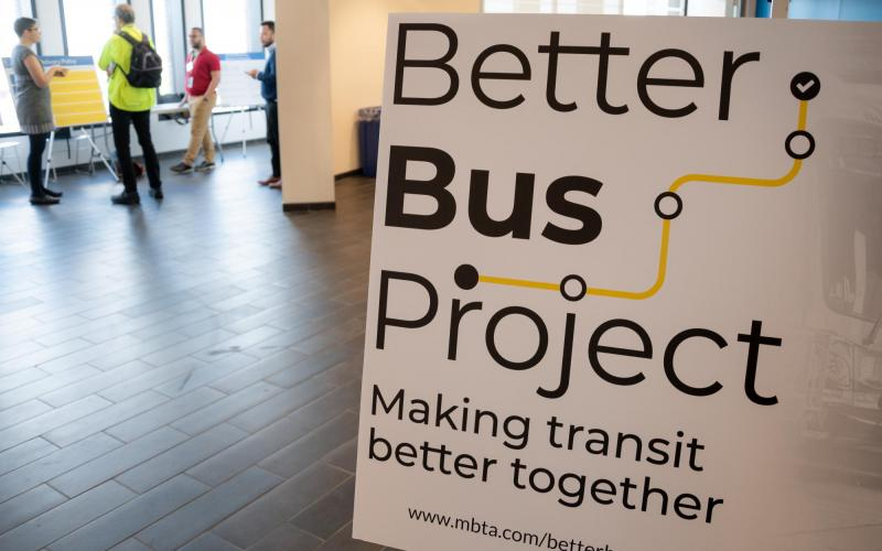 The Better Bus Project logo on a poster board, as community members talk in the background, at a public meeting in Dudley Square