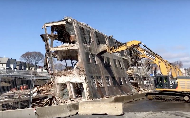 An excavator gives a final push during demolition of the Homans Building in Somerville.