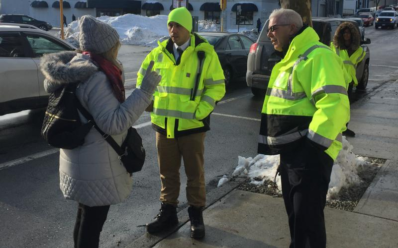 At Wollaston Station, support staff in fluorescent vests answer a customer's question.