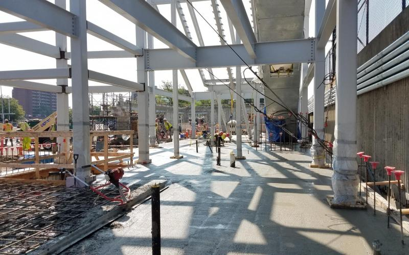 Amid sunlight, a crew lays concrete during Wollaston Station construction