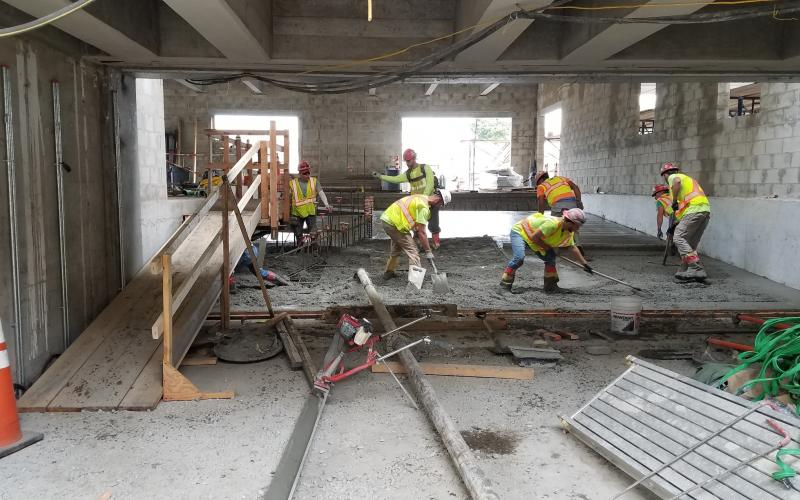 A crew lays down concrete to install a ramp during Wollaston Station construction